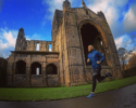 Oly running past Kirkstall Abbey in a blue jacket