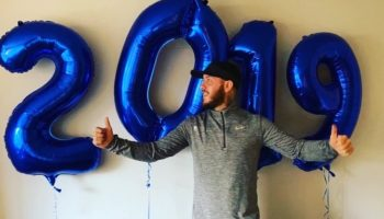 Oly in front of 4 blue balloons spelling 2019