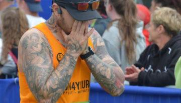 Oly in an orange running vest complete Endure24 with head in hands