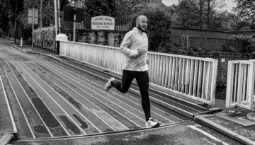 Black and white image of Oly running over a bridge